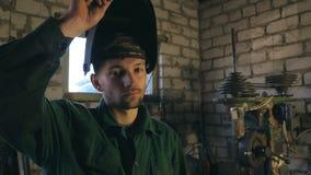 Mekanikern öppnar maskeringen, når han har avslutat hans arbete Den tröttade mannen ser in i kamera Grabb med skägget som arbetar arkivfilmer