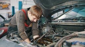 Mekanikern arbetar under huven av bilen lager videofilmer