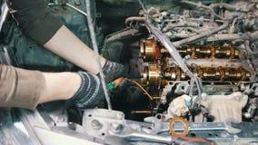 Mekanikern demonterar motorn av en bil, bilreparationen, disassembly av motorn som arbetar i seminariet lager videofilmer