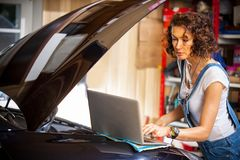 Mekanikern diagnostiserar arbetena för bilmotorn Royaltyfria Bilder