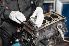 Mekanikern installerar en ny pistong Demonter medlet för motorkvarteret Motorisk huvudreparation Sexton ventiler och fyra Arkivfoto