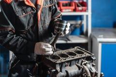 Mekanikern installerar en ny pistong Demonter medlet för motorkvarteret Motorisk huvudreparation Sexton ventiler och fyra Royaltyfria Foton
