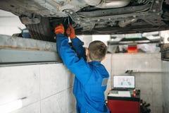 Mekanikern justerar hjulvinklarna på ställning royaltyfria bilder