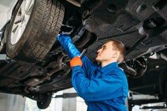 Mekanikern med lampan kontrollerar bilbromsslangar royaltyfria bilder