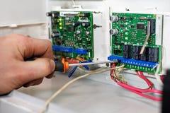Mekanikern på kontroll och mäta apparater gör reparation och justering av utrustningen Handen av arbetaren med royaltyfri fotografi