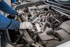 Mekanikern räcker att kontrollera upp av användbarhet av bilen i öppen huv, slut upp fotografering för bildbyråer