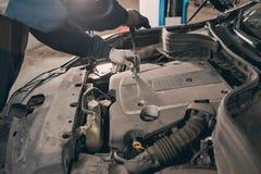 Mekanikern räcker att kontrollera upp av användbarhet av bilen i öppen huv, upp Arkivfoton