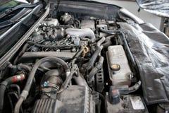 Mekanikern räcker att kontrollera upp av användbarhet av bilen i öppen huv, upp Royaltyfri Bild
