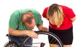 Mekanikern reparerar hjulet av en cykel Royaltyfri Foto