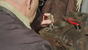 Mekanikern reparerar motorn av den gamla bilen stock video