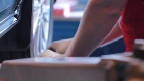 Mekanikern skruvar bilhjulet Bilreparationsstation arkivfilmer