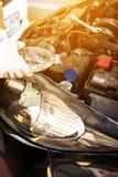 Mekanikerpåfyllningssötvatten in i vindrutan eller i torkare för vattenbehållare Royaltyfri Fotografi