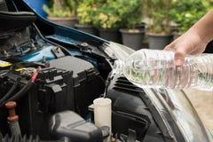 Mekanikerpåfyllningssötvatten in i vindrutan eller i torkare för vattenbehållare Arkivbilder