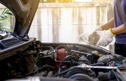 Mekanikerpåfyllningssötvatten in i vindrutan eller i torkare för vattenbehållare på bilmaskinrum Arkivfoton