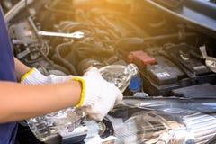 Mekanikerpåfyllningssötvatten in i vindrutan eller i torkare för vattenbehållare på bilmaskinrum Royaltyfria Bilder