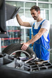 Mekanikerrepairman som installerar bilhjulet på däcket arkivbild