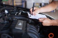 Mekanikerrepairman som kontrollerar bilen fotografering för bildbyråer