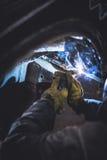 Mekanikersvetsning på en bil i en auto tjänste- reparation shoppar Fotografering för Bildbyråer