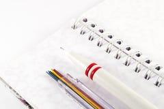 Mekanisk blyertspenna med blyertspennablytak på den vita anteckningsboken Royaltyfri Bild