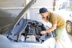 Mekanisk fixa bil hemma Reparera servicerådgivning vid mobiltelefonen Mekaniker teknikerman som kontrollerar bilmotorn service fö arkivfoto