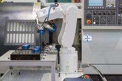Mekanisk handrobot som arbetar med CNC-drejbänkmaskinen royaltyfri bild