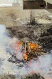 Mekanisk multivalveclamshellbrottning med glödheta stycken av järn från melten på en bakgrundsavdunstning av den smälta vätskeiro arkivbild