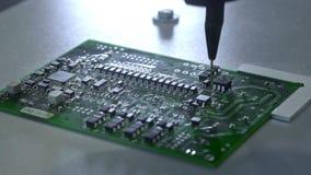 Mekanisk skapelseprocess av elektroniska str?mkretsar Skapa ett elektroniskt bräde Metallvisaren ställer in chiperna på a arkivfilmer