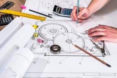 Mekanisk tekniker med arbete på tekniska teckningar och arbetshjälpmedel, Fotografering för Bildbyråer