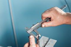 Mekaniska teknikerarbetarhänder som mäter detaljhjälpmedlet, når att ha bearbetat på seminariet med glidningsklämman arkivbilder