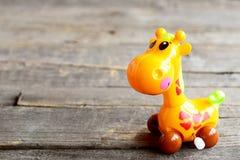 Mekaniskt spola upp den plast- giraffleksaken Nätt urverkbarnleksak på gammal träbakgrund Rolig barnbakgrund royaltyfri fotografi