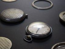 Mekanism av klockor och deras delar på en svart bakgrund arkivfoto