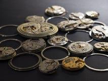 Mekanism av klockor och deras delar på en svart bakgrund royaltyfria bilder