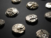 Mekanism av klockor och deras delar på en svart bakgrund royaltyfri foto