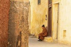 MEKNES, MARROCOS - 18 DE FEVEREIRO DE 2017: Homem não identificado que senta-se na rua de Meknes, Marrocos Meknes é um dos quatro Foto de Stock