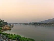 Mekong ποταμός και γέφυρα που διασχίζουν στο Λάος στο βράδυ με το ηλιοβασίλεμα και τον κίτρινο ουρανό Στοκ εικόνες με δικαίωμα ελεύθερης χρήσης