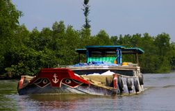 MEKONG DELTA, VIETNAM: DECEMBER 30. 2014: Overloaded sampan style boat with typical stylized bow eyes royalty free stock photos