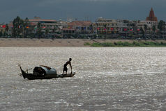 The Mekong River. A boat travels along the muddy Mekong River in Phnom Penh, Cambodia Royalty Free Stock Photos