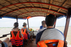 Mekong River Boat Tour. Western and Asian tourists on a boat cruise on the Mekong River in South Vietnam royalty free stock photo