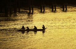 Mekong River traditional boat during sunset. Four people