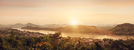 Mekong River At Sunset Panorama. Overlooking the river banks of the Mekong from a high viewpoint. Warm sunset and some mountains in the background Royalty Free Stock Photos
