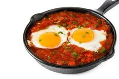 Meksykański śniadanie: Huevos rancheros w żelaznej smaży niecce odizolowywającej zdjęcia stock
