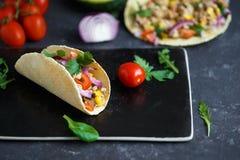 Meksykański tacos z wieprzowiną, warzywami i pikantność na czarnym kamienia talerzu na ciemnym tle z składnikami dla tacos, zdjęcia royalty free