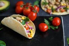 Meksykański tacos z wieprzowiną, warzywami i pikantność na czarnym kamienia talerzu na ciemnym tle z składnikami dla tacos, zdjęcia stock