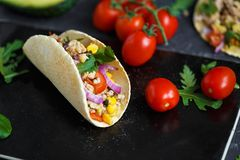 Meksykański tacos z wieprzowiną, warzywami i pikantność na czarnym kamienia talerzu na ciemnym tle z składnikami dla tacos, obrazy royalty free