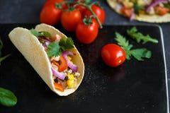Meksykański tacos z wieprzowiną, warzywami i pikantność na czarnym kamienia talerzu na ciemnym tle z składnikami dla tacos, fotografia stock