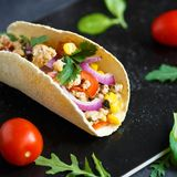 Meksykański tacos z wieprzowiną, warzywami i pikantność na czarnym kamienia talerzu na ciemnym tle z składnikami dla tacos, zdjęcie royalty free