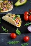 Meksykański tacos z wieprzowiną, warzywami, pomidorami, avocado i pikantność na czarnym kamienia talerzu na ciemnym tle z składni zdjęcia stock