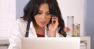 Meksykanina doktorski opowiadać na jej smartphone w biurze Zdjęcie Royalty Free