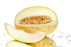 Melão cortado amarelo com as sementes no fim branco do fundo do espelho acima fotografia de stock royalty free