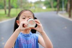 Melão da bebida da menina da garrafa de vidro fora foto de stock royalty free
